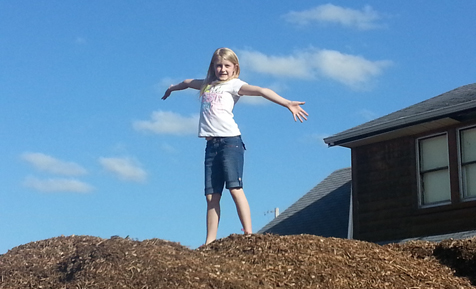 Girl standing on top of a pile of mulch